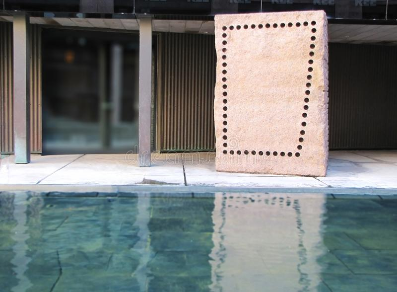 Perforated brown rectangular shaped stone reflecting in water stock photography