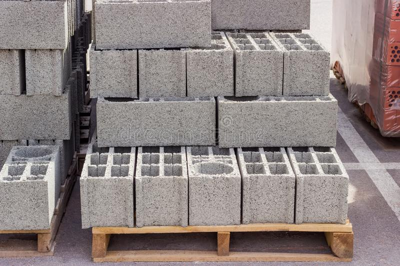 Perforated concrete masonry units on pallet on an outdoor warehouse. Perforated concrete masonry units on a wooden pallets among other building materials on an stock images