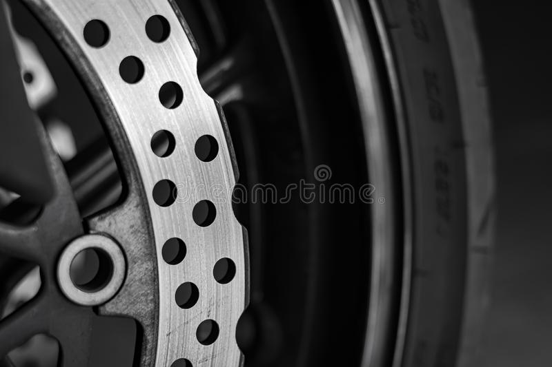 Perforated disc brake on sport motorcycle front wheel. Perforated brake disc of a front wheel of a sports motorcycle in the foreground stock images