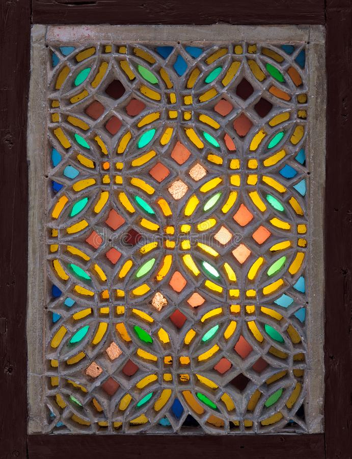 Stucco window decorated with colorful stain glass with geometrical circular patterns, an Ottoman era tradition royalty free stock photo