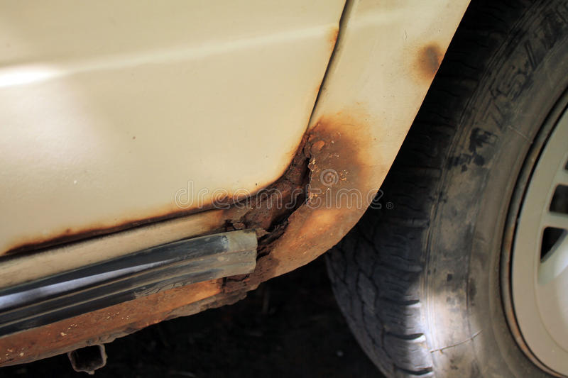 Perforating corrosion of old car`s threshold. Visible through hole with paint peeling stock images
