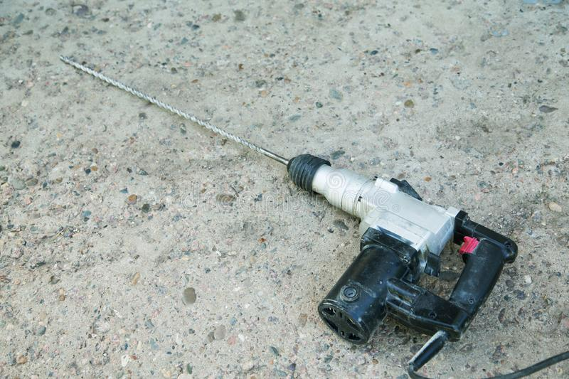 Perforator with a long drill rests on a concrete. Surface stock image