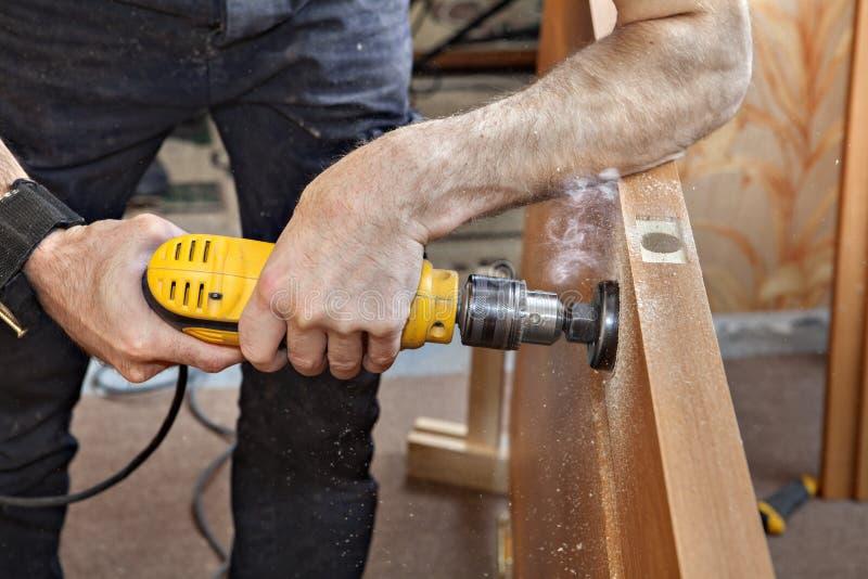 Perforazione del foro della serratura del trapano elettrico attraverso la porta, per il chiavistello senza molla di scatto, c fotografie stock