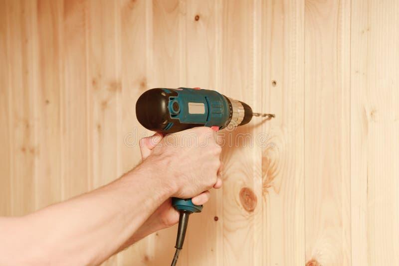 Perfore adentro las manos de un trabajador que perfora una pared fotografía de archivo