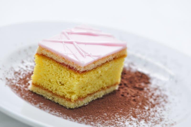 Perfore la torta con el polvo de cacao en la placa blanca, fotografía para la tienda, pastelería fotografía de archivo