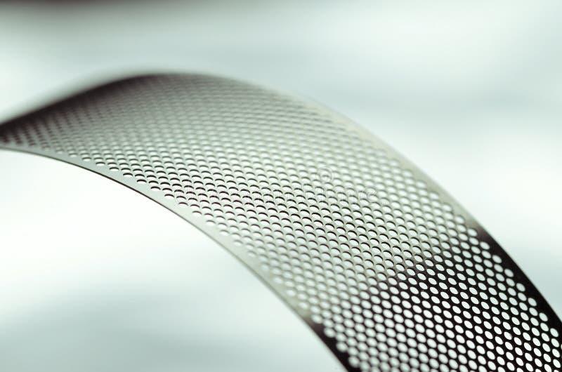 Perforerat band för metall, krökt abstrakt begrepp arkivfoto