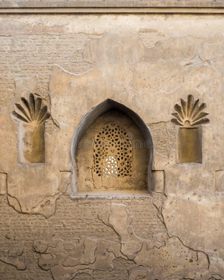 Perforerat välvt stuckaturfönster som dekoreras med blom- modeller, yttre vägg av moskén av Ibn Tulun, medeltida Kairo, Egypten royaltyfri foto