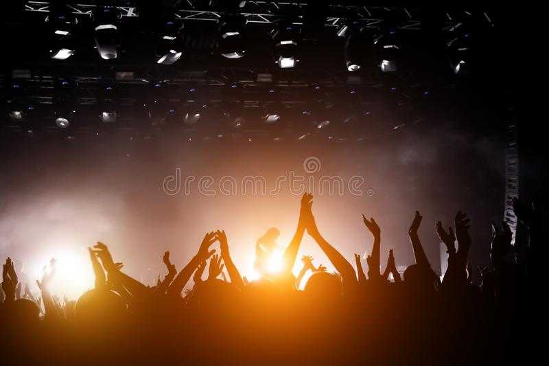 Performace of a popular group. Crowd is dancing and having fun. Bright spotlig royalty free stock photography