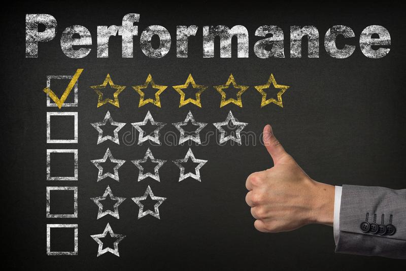 Performance five 5 star rating. thumbs up service golden rating stars on chalkboard stock photo