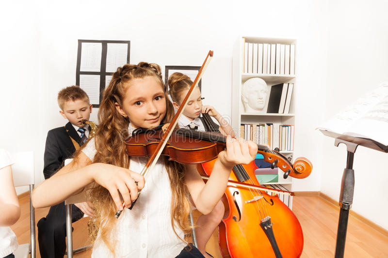 Performance of kids playing musical instruments. Performance of cheerful children playing musical instruments together in musical school royalty free stock photography