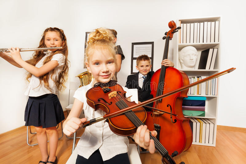 Performance of kids who play musical instruments. Performance of children who play musical instruments together in musical school royalty free stock photo