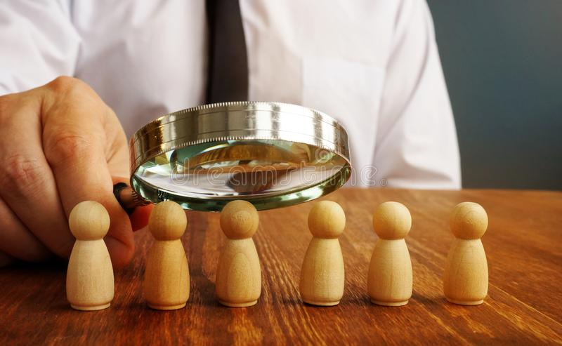 Performance review. Man with magnifying glass evaluate figurines as symbol of employee royalty free stock photography