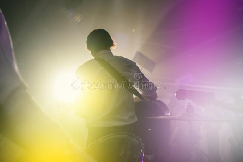 Performance of a rock band at a concert or party. Silhouettes of musicians, guitarist and drummer. People dance to the music, the. Light from the spotlights stock image
