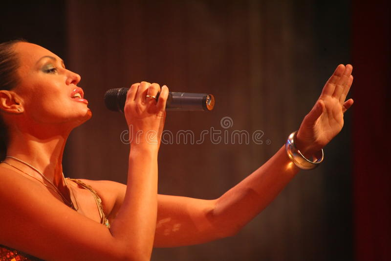 The performance on the stage actress and singer of russian classical crossover diva Larisa Lusta. Beautiful singer singing with microphone. The performance on stock photography