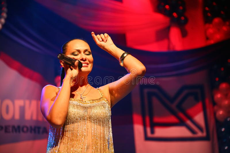 The performance on the stage actress and singer of russian classical crossover diva Larisa Lusta. Beautiful singer singing with microphone. The performance on stock photo