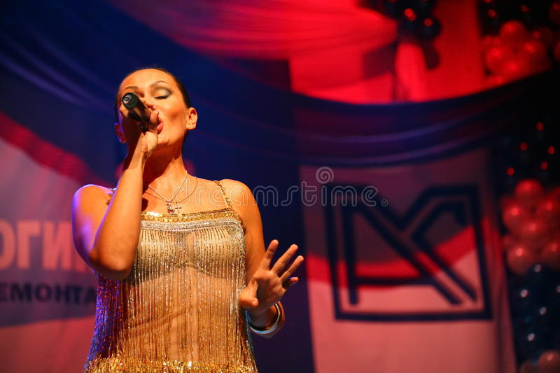 The performance on the stage actress and singer of russian classical crossover diva Larisa Lusta. Beautiful singer singing with microphone. The performance on royalty free stock photo