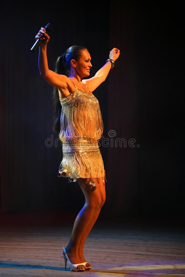 The performance on the stage actress and singer of russian classical crossover diva Larisa Lusta. Beautiful singer singing with microphone. The performance on royalty free stock image