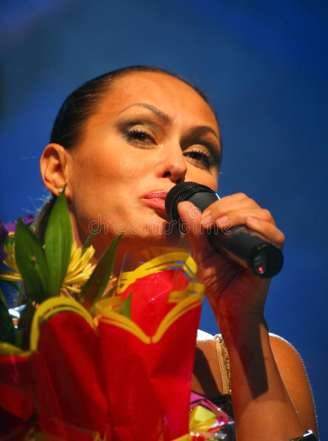 The performance on the stage actress and singer of russian classical crossover diva Larisa Lusta. Beautiful singer singing with microphone. The performance on stock image