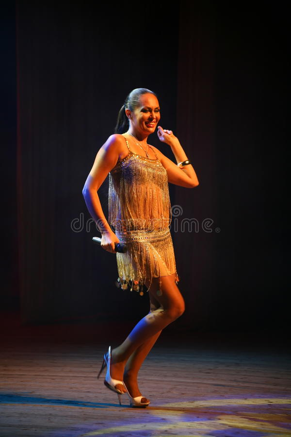 The performance on the stage actress and singer of russian classical crossover diva Larisa Lusta. Beautiful singer singing with microphone. The performance on stock photos