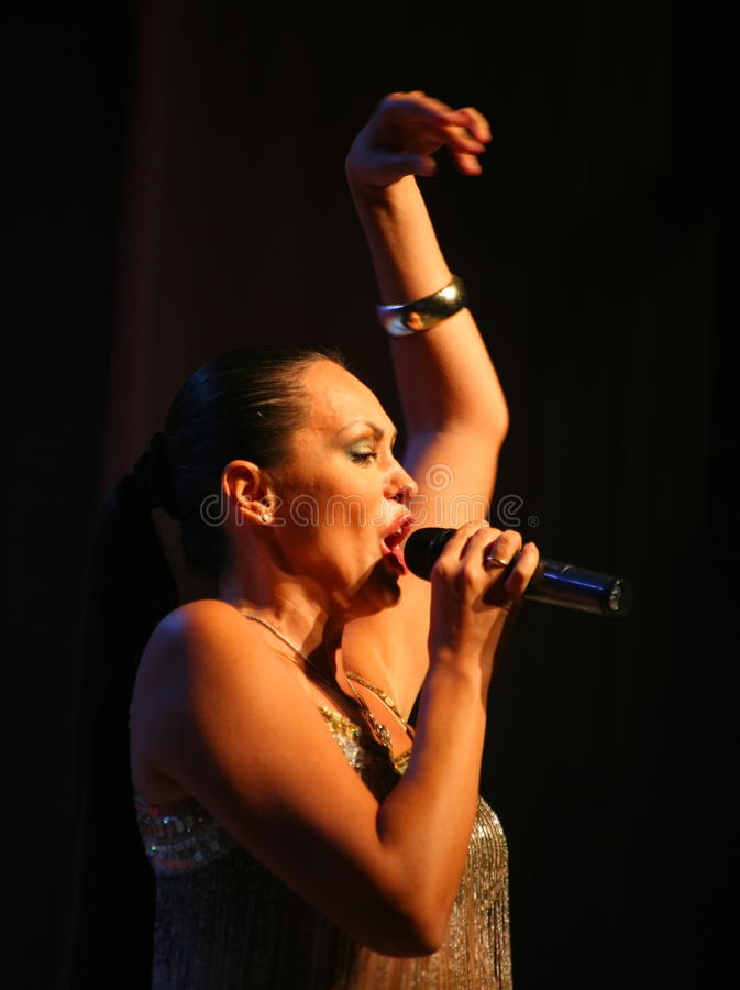 The performance on the stage actress and singer of russian classical crossover diva Larisa Lusta. Beautiful singer singing with microphone. The performance on royalty free stock photography