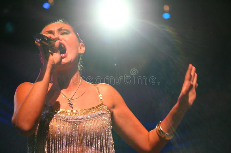The performance on the stage actress and singer of russian classical crossover diva Larisa Lusta. Beautiful singer singing with microphone. The performance on royalty free stock images