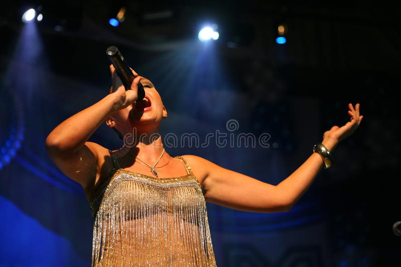 The performance on the stage actress and singer of russian classical crossover diva Larisa Lusta. Beautiful singer singing with microphone. The performance on royalty free stock photos