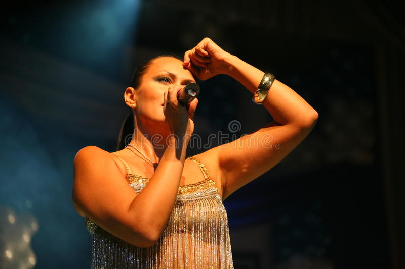 The performance on the stage actress and singer of russian classical crossover diva Larisa Lusta. Beautiful singer singing with microphone. The performance on stock images