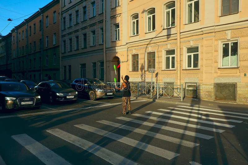 Performance of a street juggler at a pedestrian crossing in front of cars standing at the crossroads royalty free stock image
