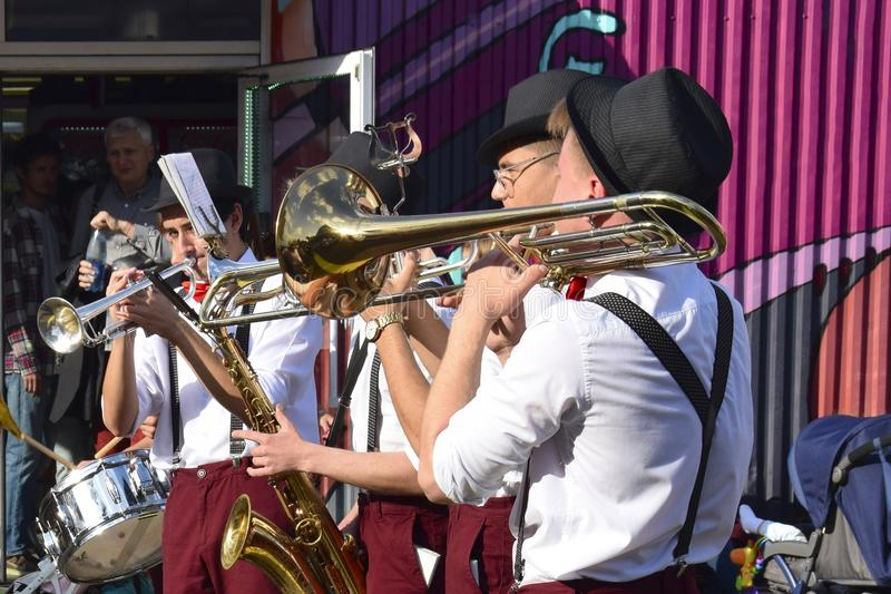 Performance of street musicians on a street in the city on the weekend. Small brass band: trumpeters, saxophonist, drummer royalty free stock photos