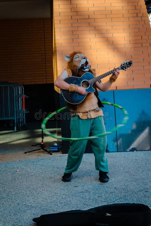 Performer hula hooping and playing a guitar in a lion mask. At Artprize stock photography