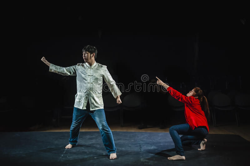 Performers acting on stage in dark studio stock photography