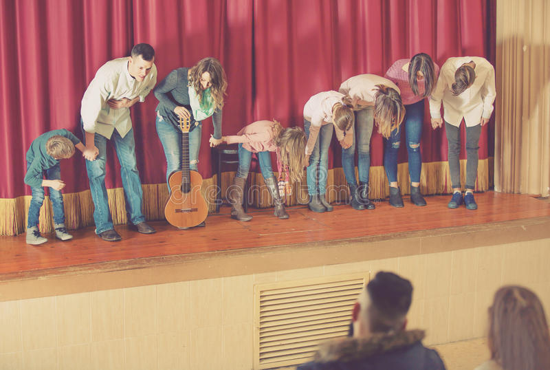 Performers bowing to audience after concert. Glad positive performers bowing to audience after concert in concert hall royalty free stock photos