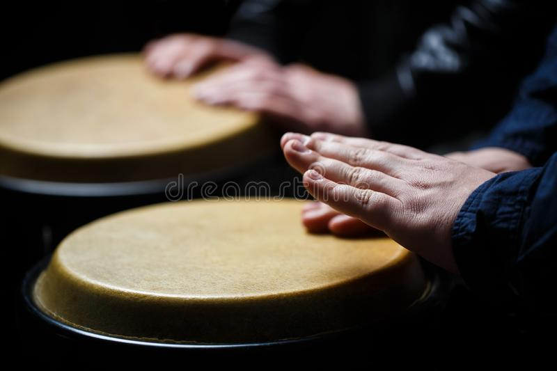 Performers playing bongo drums. Close up of musician hand playing bongos drums. Drum. Hands of a musician playing on. Bongs. Afro-Cuba, rum, drummer, fingers stock image