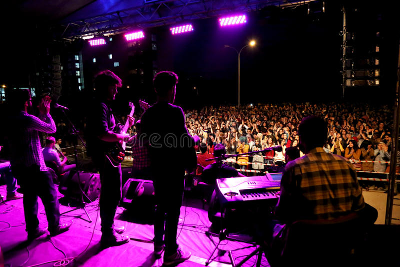 Performers on stage at concert. Performers on a stage in front of a large crowd during live concert stock photography