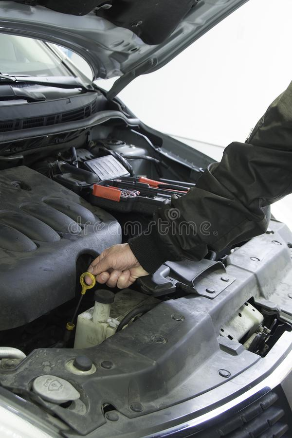 Performing car repair in a home garage to provide safe transportation. Vehicle is in a shop for repair and periodic maintenance stock image