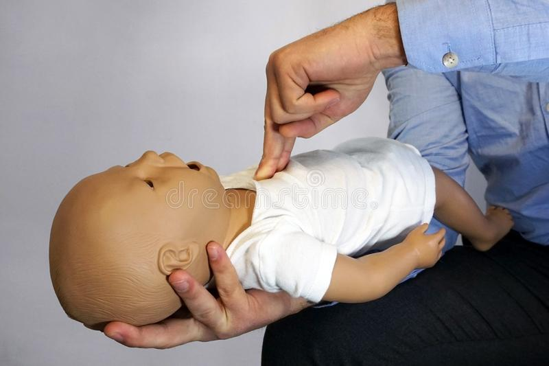 Performing cpr on a simulation mannequin baby dummy during medical training Pediatric Basic Life Support.  stock photo