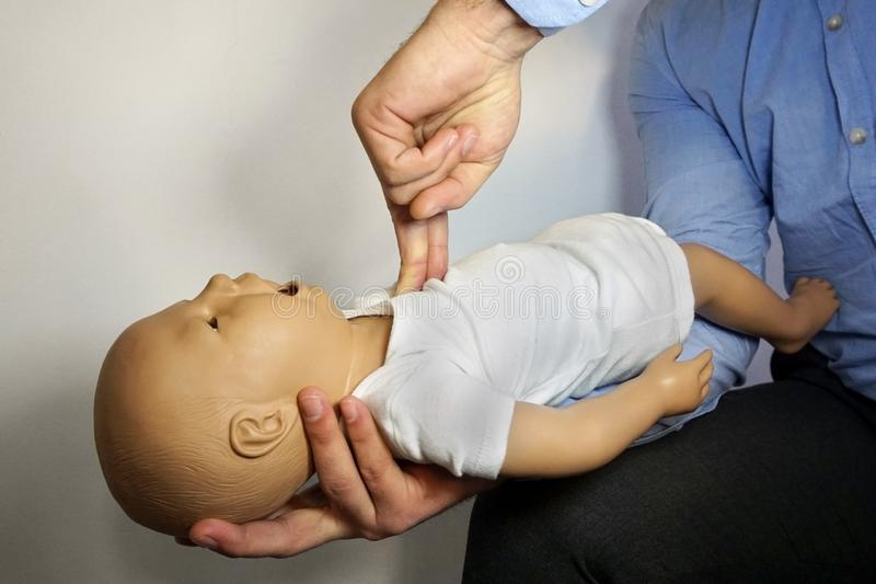 Performing cpr on a simulation mannequin baby dummy during medical training Pediatric Basic Life Support.  royalty free stock image