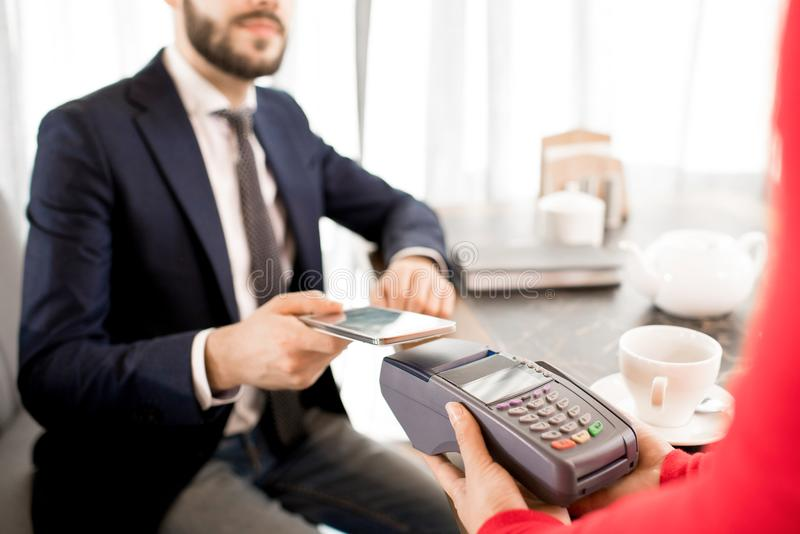 Performing transaction with gadget in restaurant. Close-up of modern businessman using contactless payment while performing transaction with smartphone in royalty free stock image
