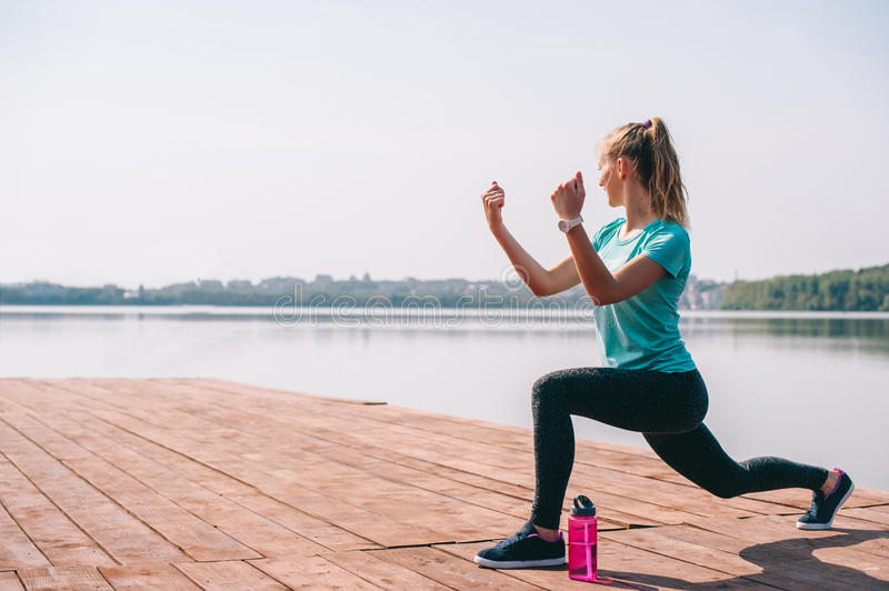 She performs exercises on pier. Training girls on the dock overlooking the horizon royalty free stock images