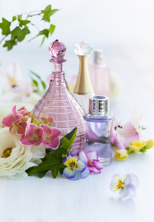Perfume and aromatic oils bottles. Surrounded by fresh flower royalty free stock image