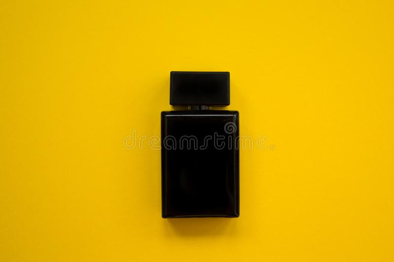 Perfume in beautiful black bottle on a yellow background, flat image stock images