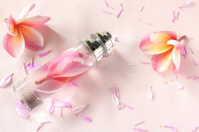 Perfume and beautiful flowers on sweet background stock image