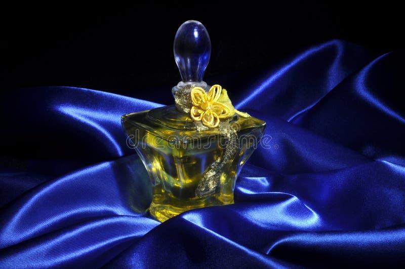 Perfume on blue satin royalty free stock photography