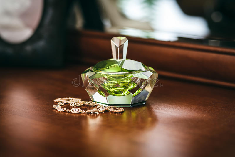Perfume bottle with a beautiful green ruby shine and jewelry on stock photos