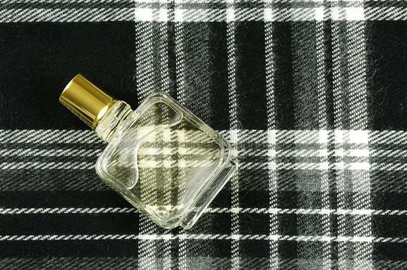 Perfume bottle on check pattern stock photography
