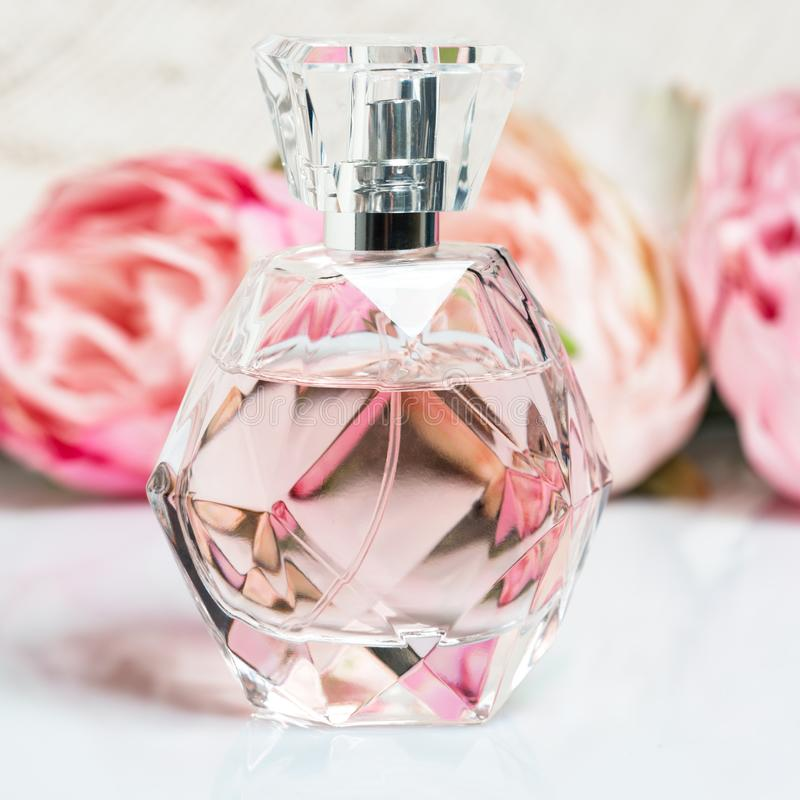 Perfume bottle with flowers on light background. Perfumery, cosmetics, fragrance collection stock photography