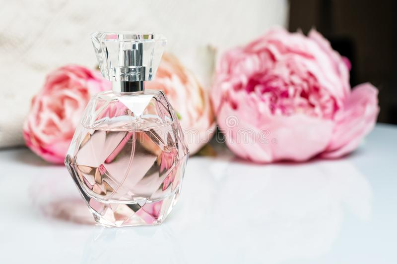 Perfume bottle with flowers on light background. Perfumery, cosmetics, fragrance collection stock images