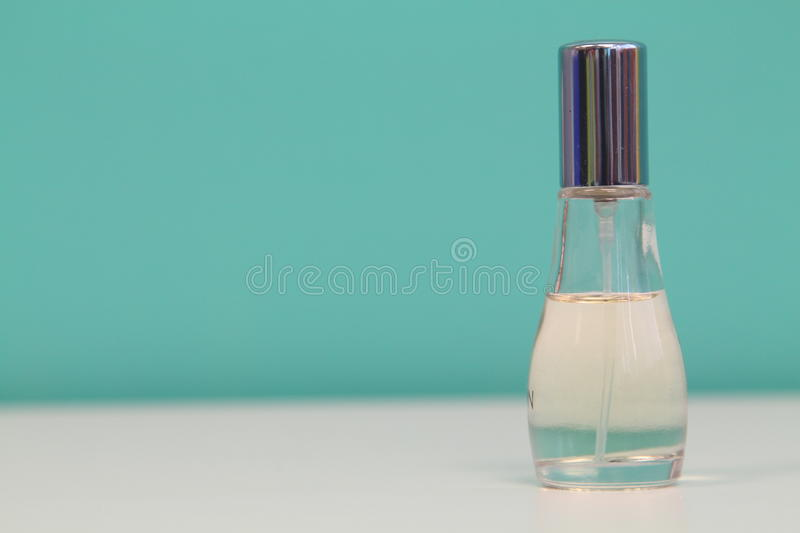 Perfume bottle with light blue cover isolated white and blue background stock photo