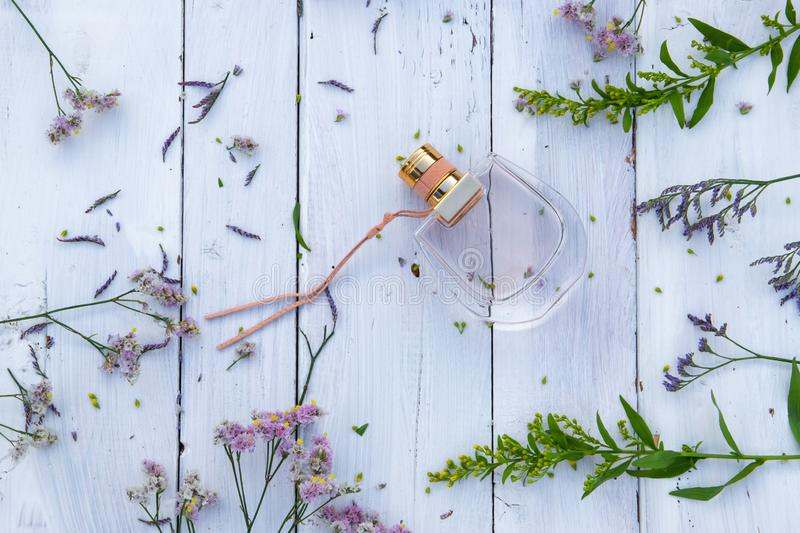 Perfume bottle surrounded by fresh flowers on wooden background stock images