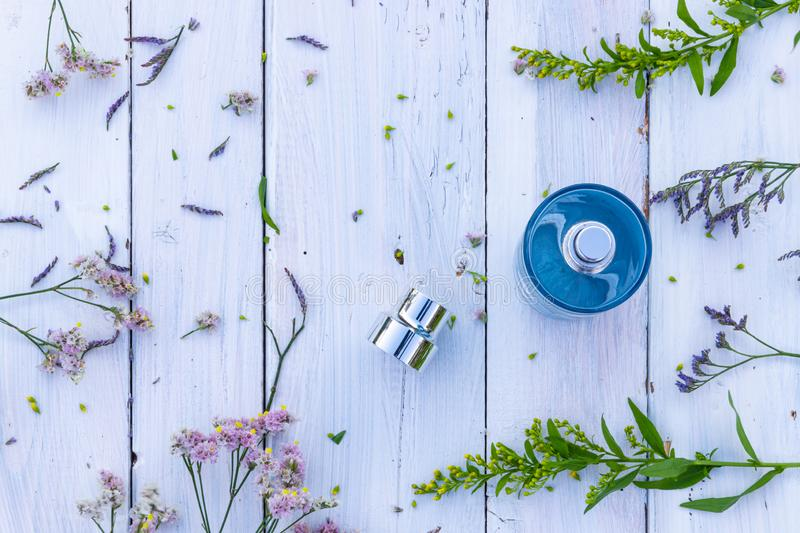 Perfume bottle surrounded by fresh flowers on wooden background stock photography